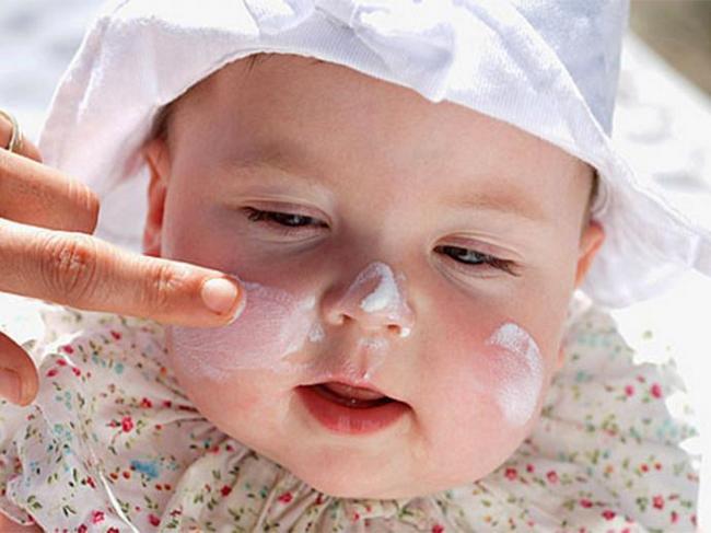 ребенку мажут щеки кремом