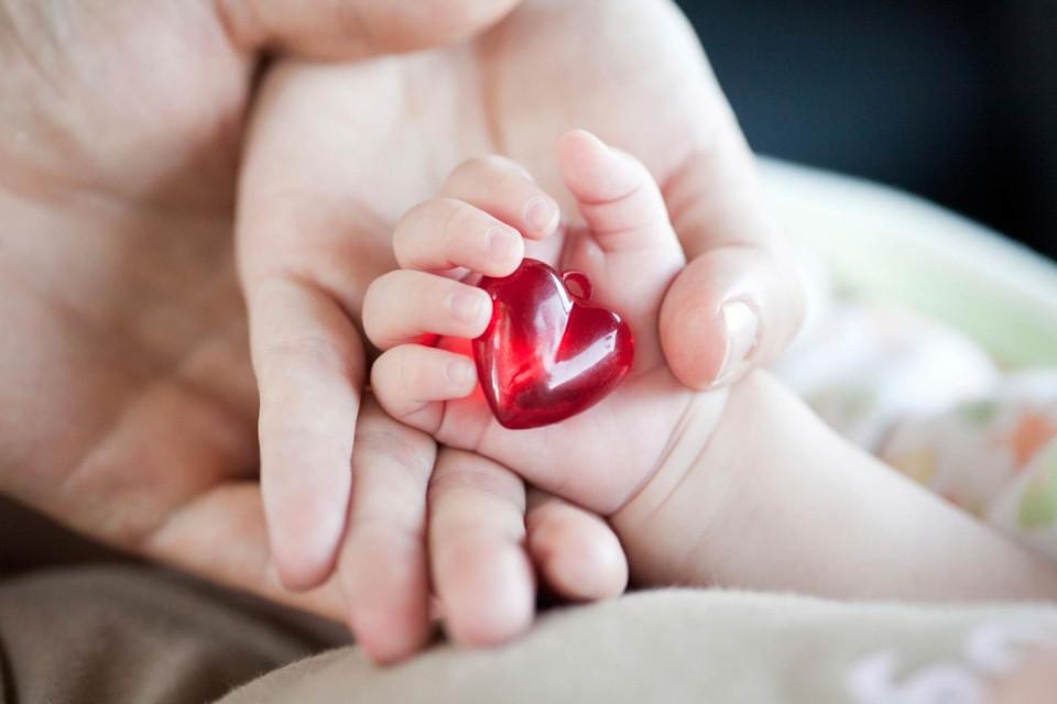 рука ребенка держит кулон в виде сердечка