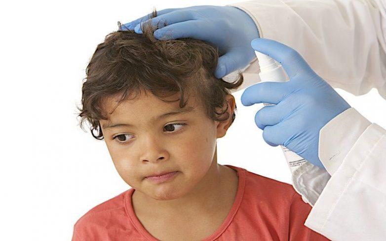 врач обрабатывает волосы ребенку