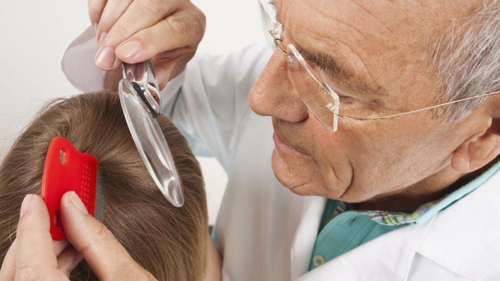 врач проводит осмотр волос ребенка