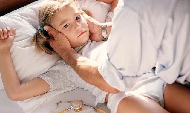 врач держит ребенка за голову