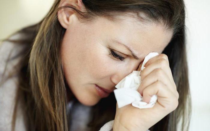 женщина вытирает глаз платком