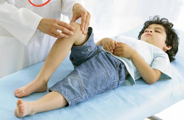 врач осматривает колено ребенка