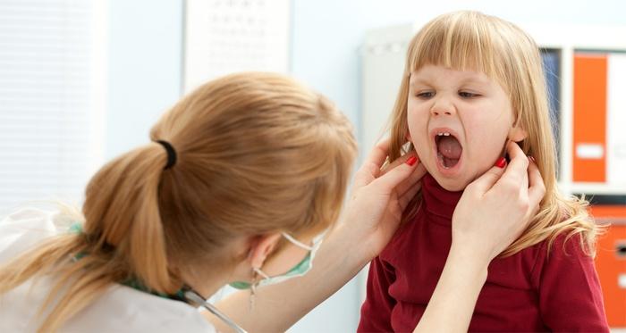 Врач диагностирует у ребенка вирус Эпштейна-Барр