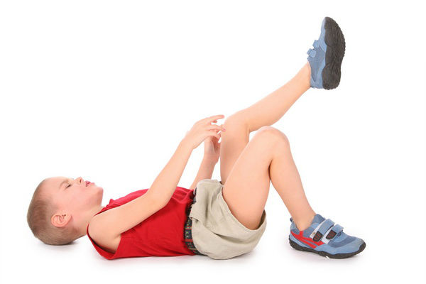ребенок лежит и держится за колено