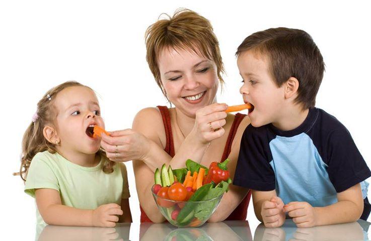 женщина кормит детей овощами