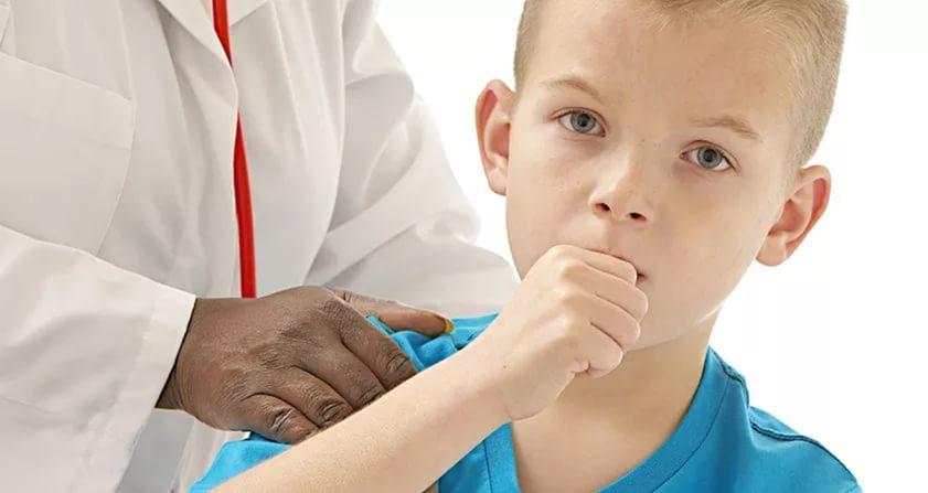 врач держит за плечо кашляющего мальчика