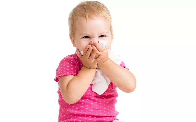 маленький ребенок высмаркивается в платок