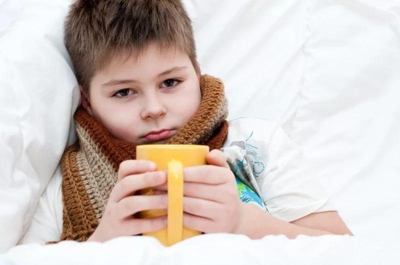 ребенок лежит в кровати с чашкой