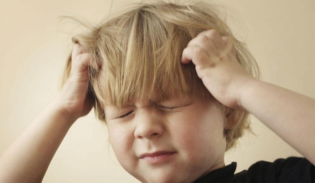 ребенок зажмурился и держится за голову