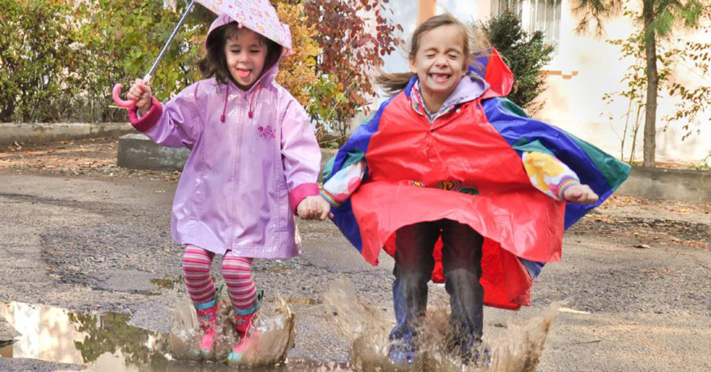 дети прыгают по луже