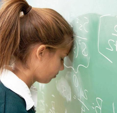 девочка уткнулась лбом в школьную доску
