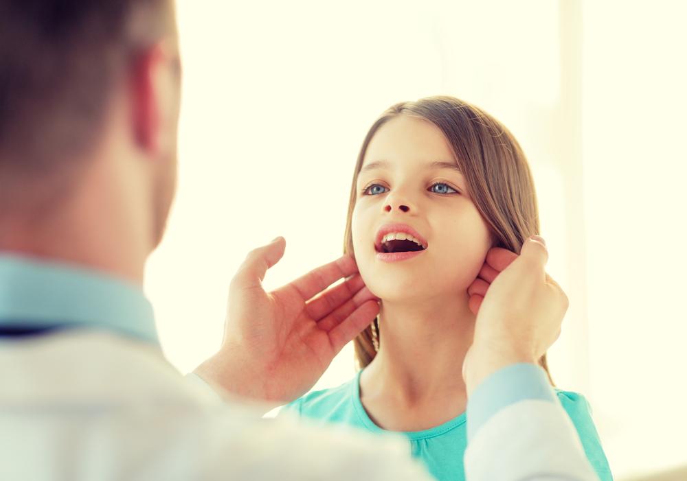 врач пальпирует шею девочки