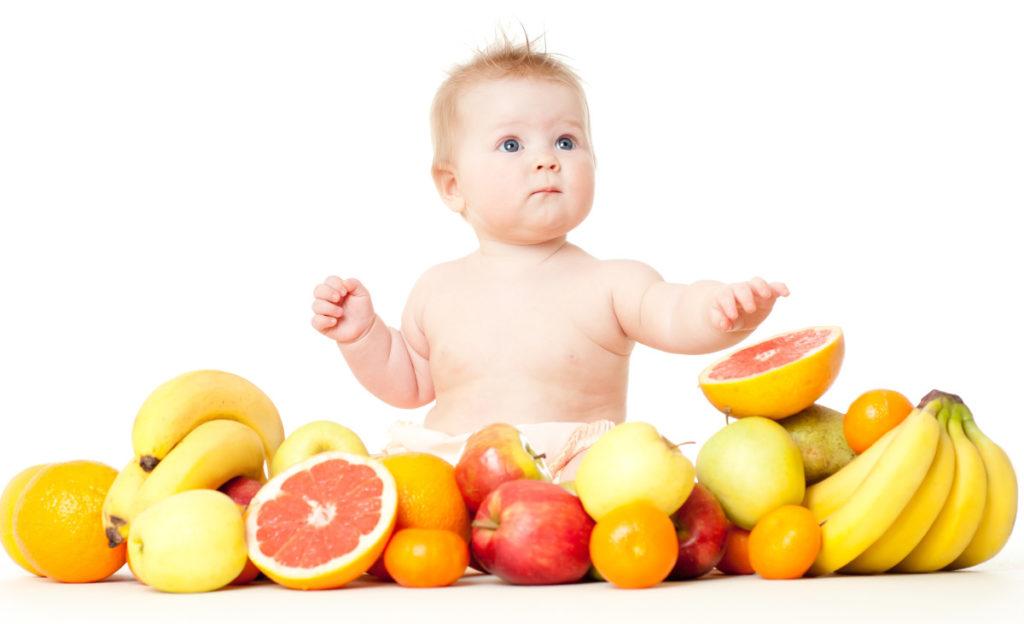 ребенок сидит в фруктах