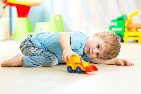 ребенок играется игрушечной машинкой