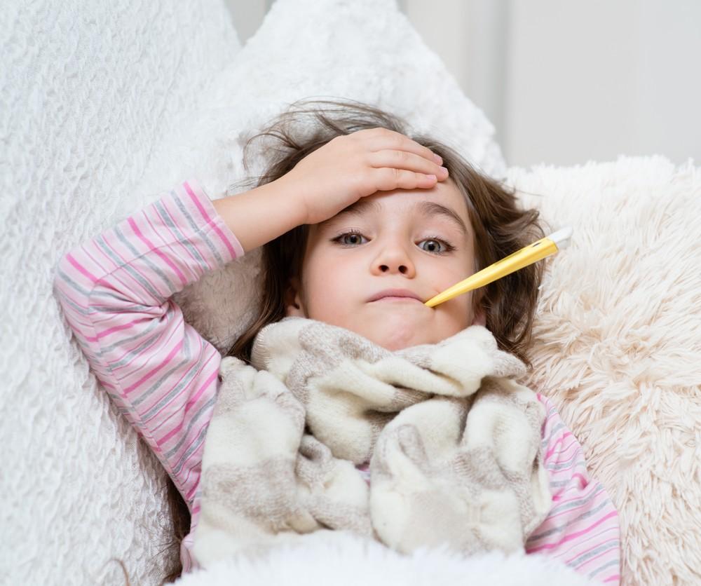 ребенок лежит с градусником во рту