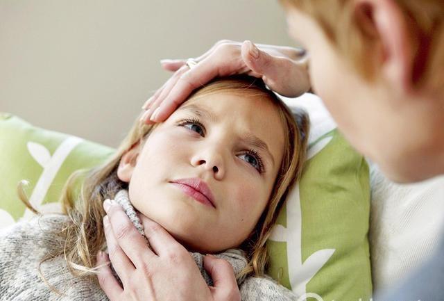 мама пробует горло и лоб больного ребенка