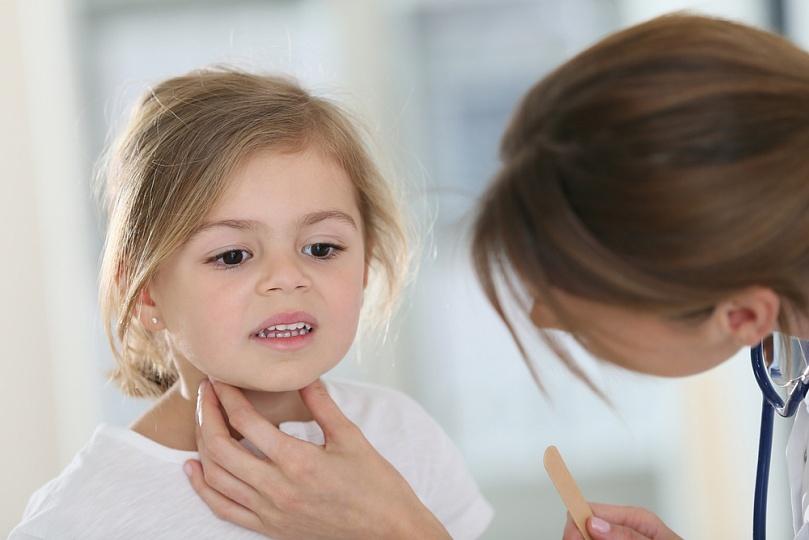 врач ощупывает горло ребенка