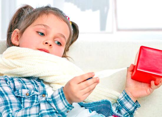 девочка с больным горлом смотрит на градусник