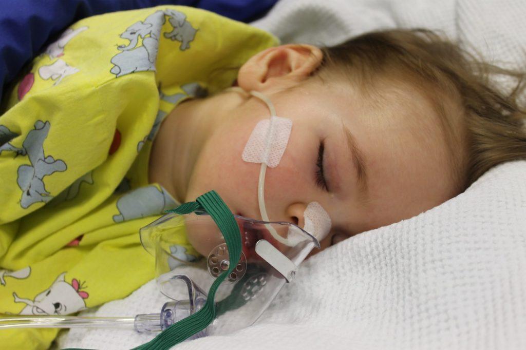 ребенок дышит через медицинский прибор