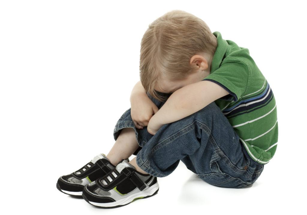 ребенок закрыл лицо коленями