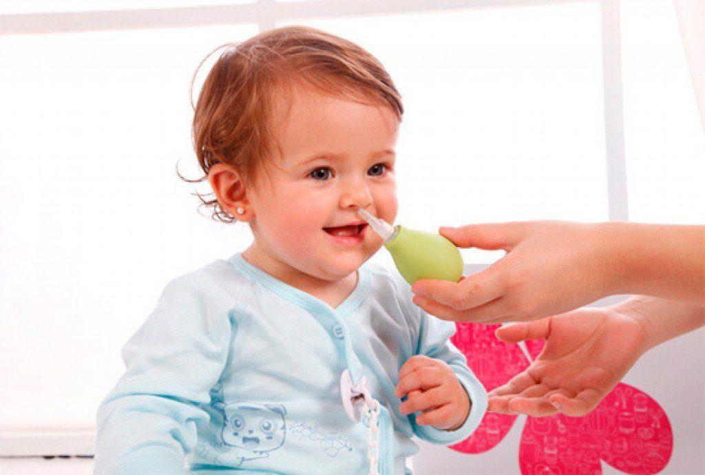 ребенку прочищают нос грушей