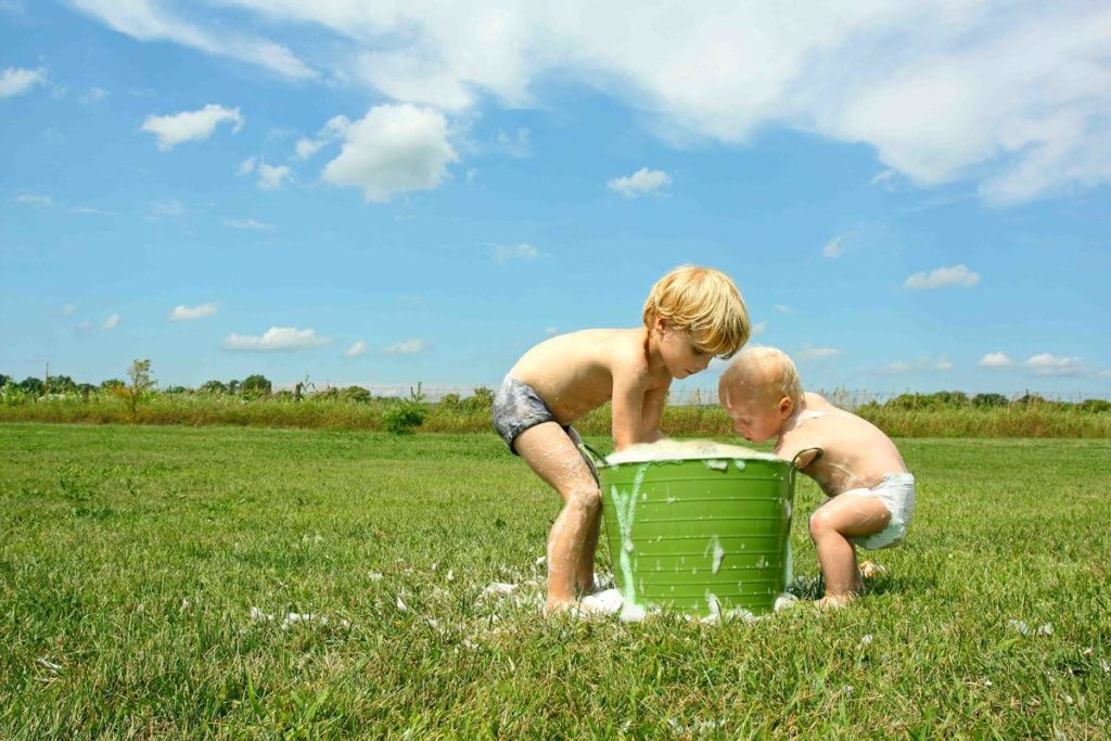 дети стирают в ведре на лугу