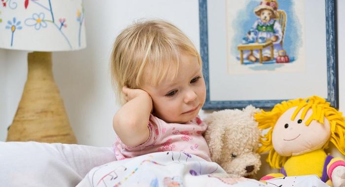 девочка прижимает руку к ушку