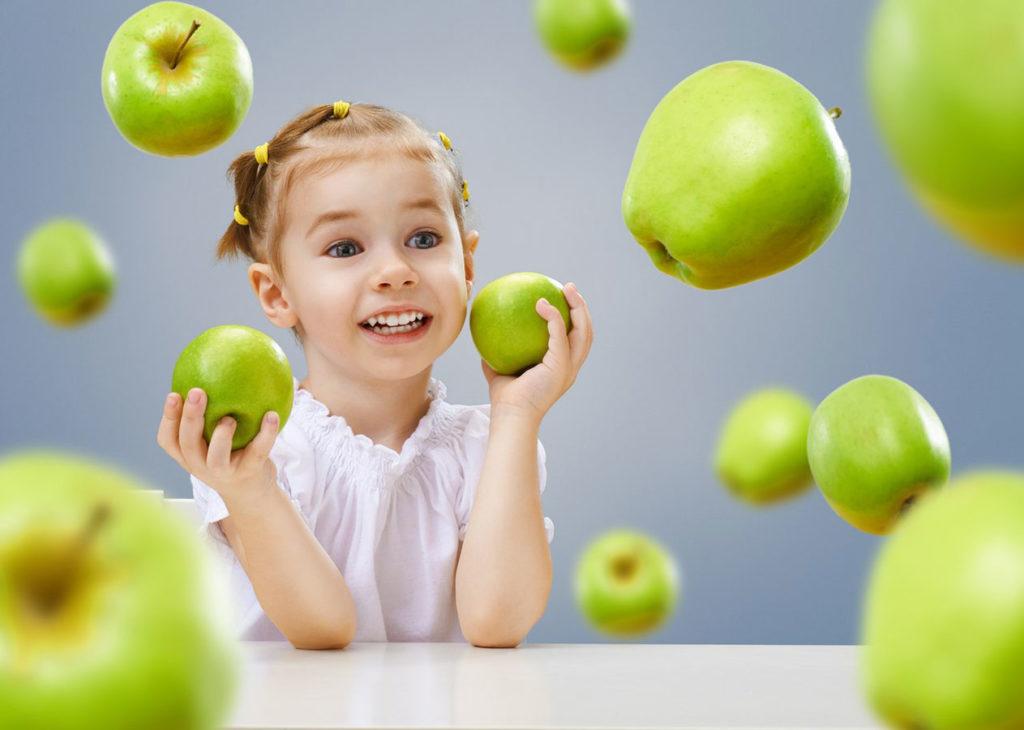 девочка держит в руках зеленые яблоки