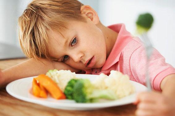 мальчик лежит на столе перед тарелкой с едой