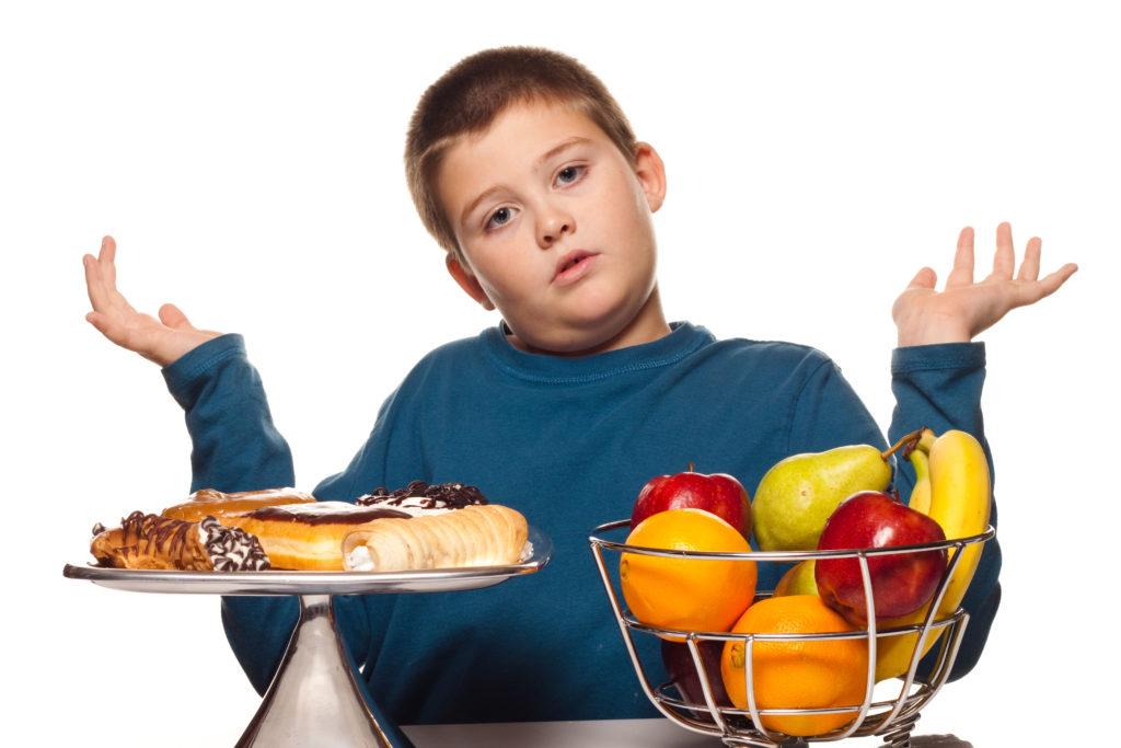 толстый мальчик перед мисками с тортом и фруктами