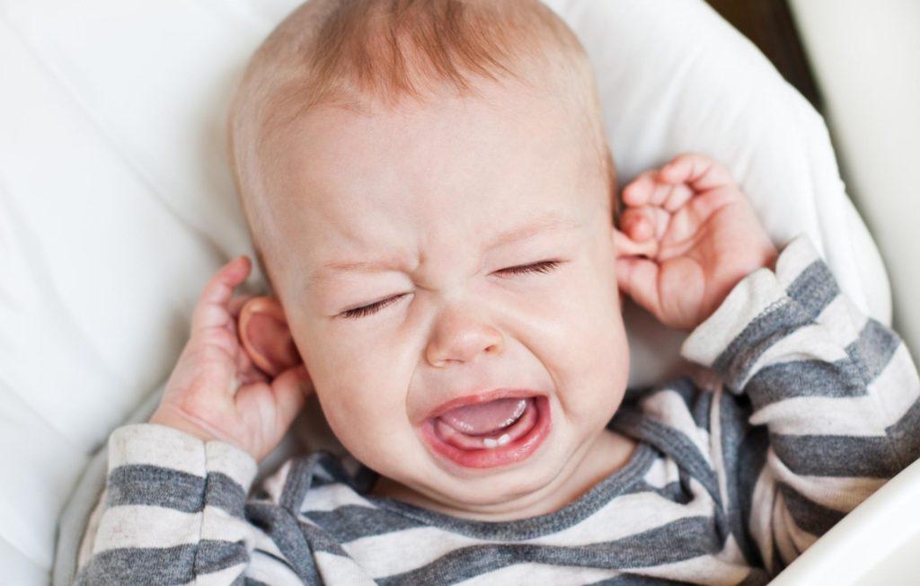 ребенок держится за ушки и плачет