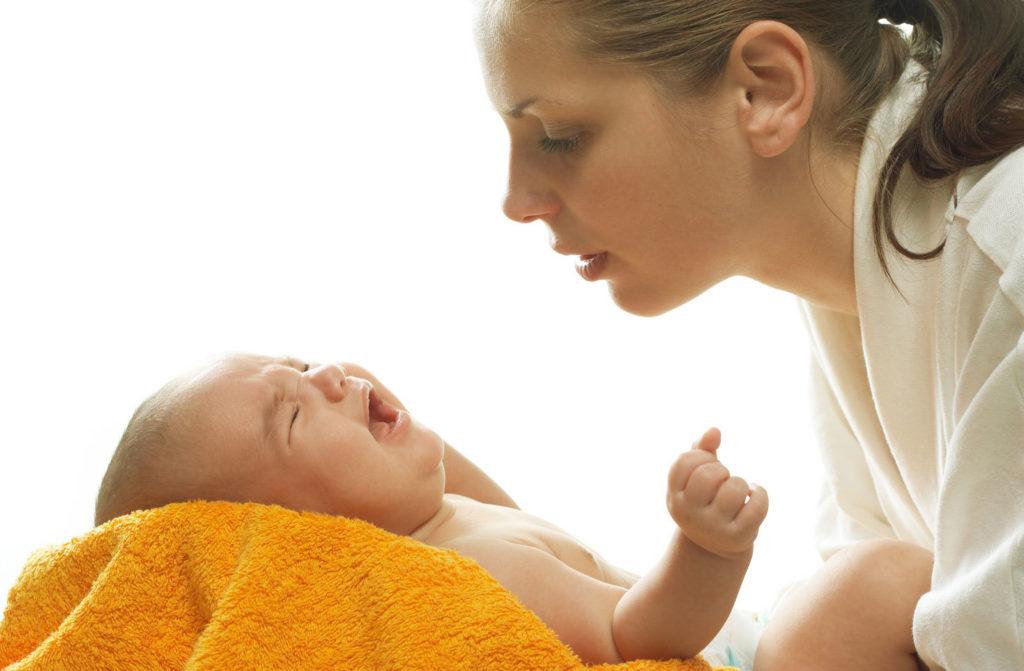 грудной ребенок плачем, женщина его держит