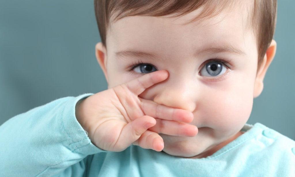 ребенок закрывает лицо ручкой