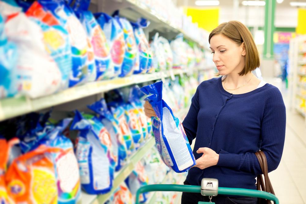 женщина выбирает стиральный порошок