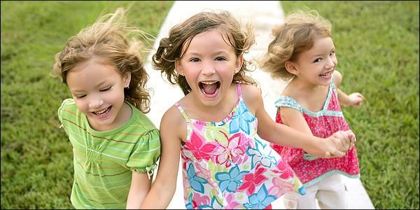 три девочки держатся за руки и улыбаются