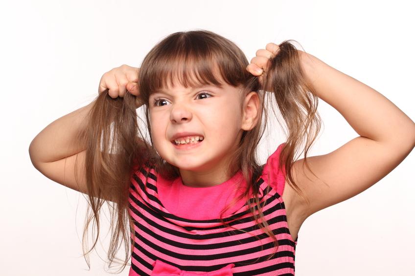 девочка тянет себя за волосы