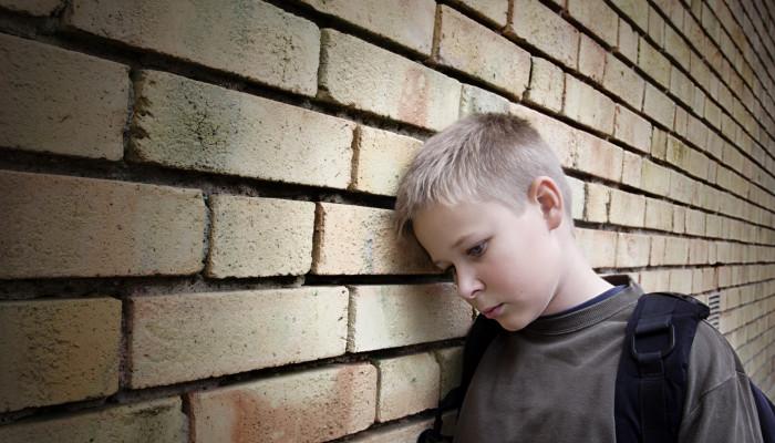 мальчик прислонился головой к стене