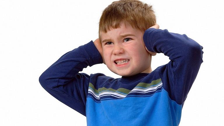 мальчик закрыл уши руками