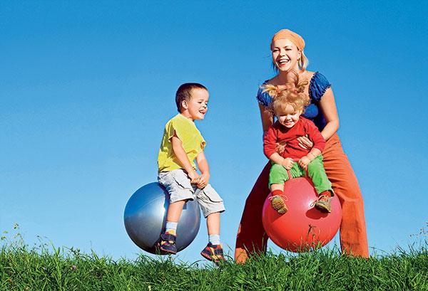 мама и дети прыгают на мячах-прыгунах