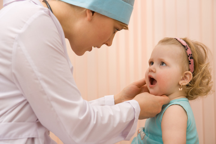 доктор смотрит горло малышу