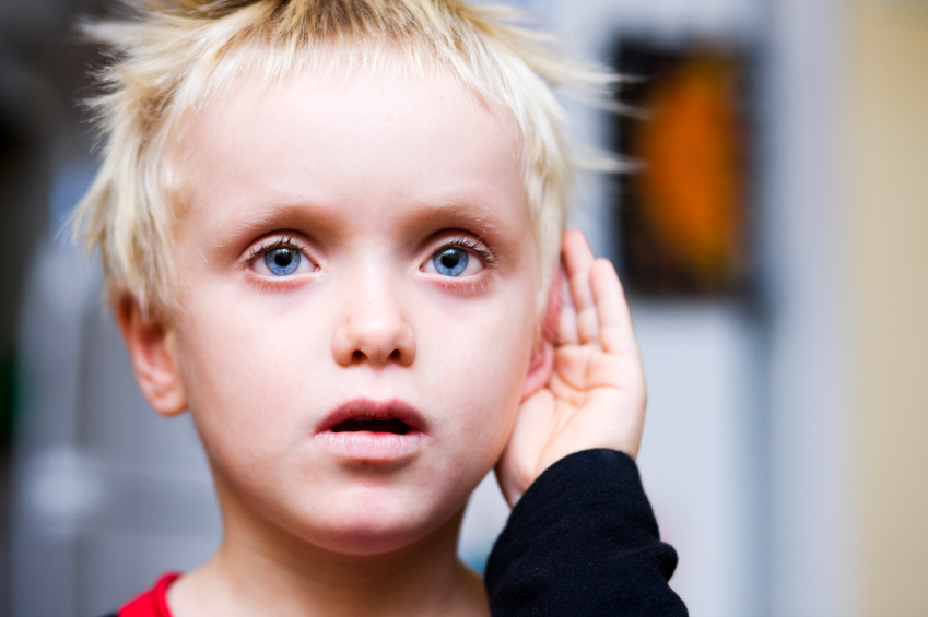 мальчик приложил руку к уху, слушает