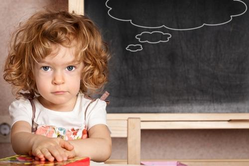 девочка сидит рядом со школьной доской