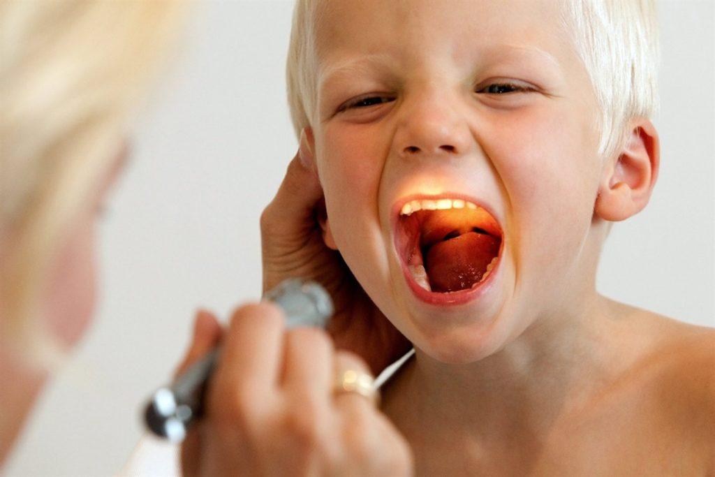 врач смотрит ребенку горло