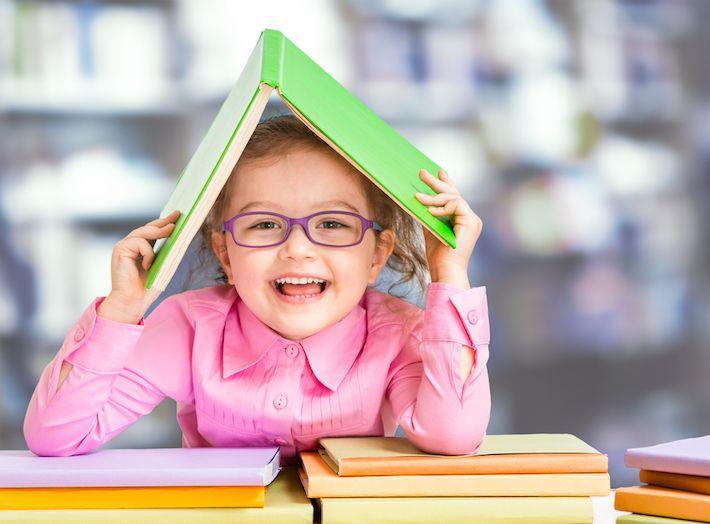 ребенок в очках держит над головой книжку