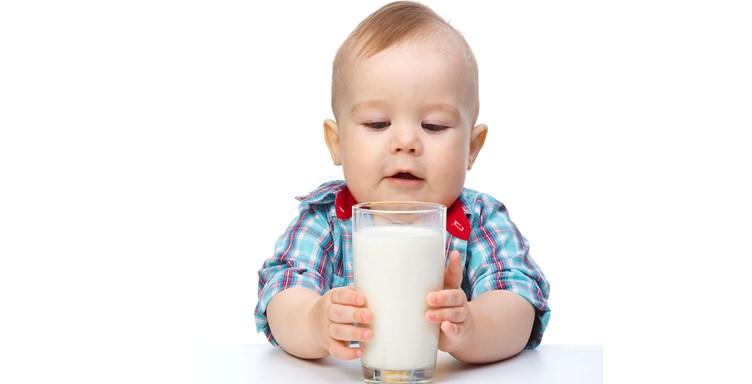 малыш держит стакан с молоком