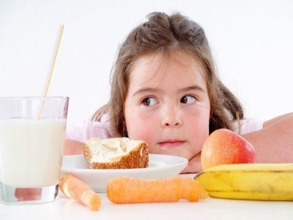 девочка смотрит на стакан с молоком