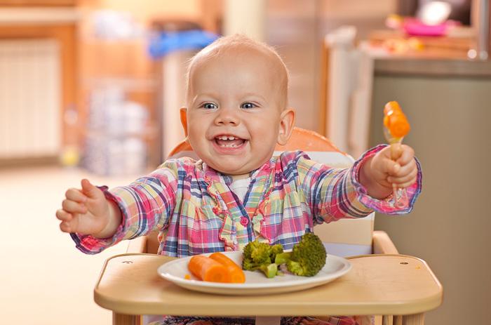 малыш улыбается в стульчике для кормления