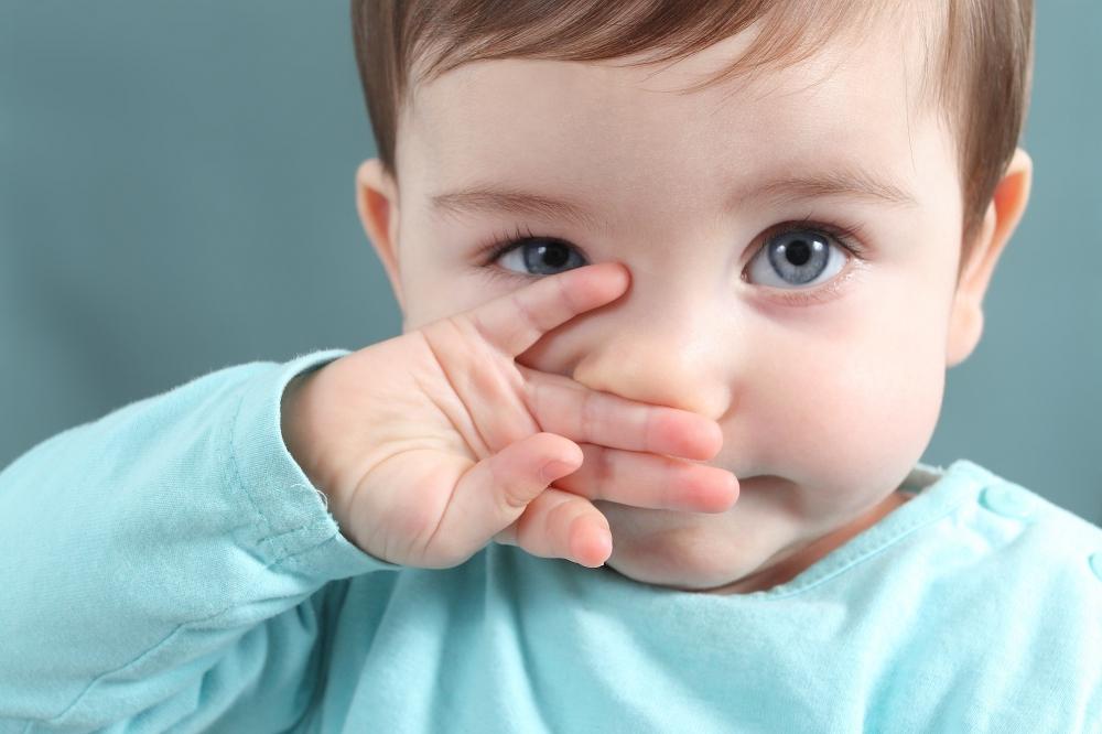 мальчик закрывает нос рукой