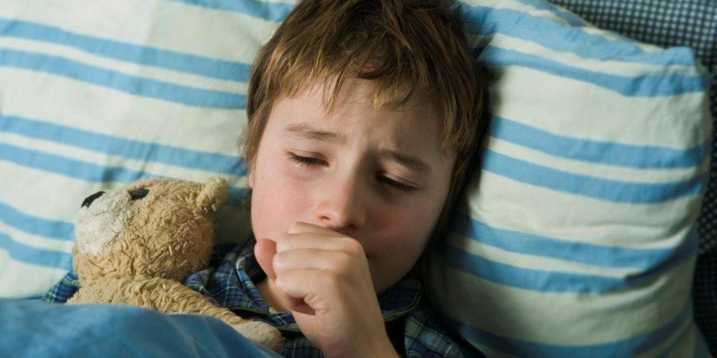 мальчик лежит в постели, кашляет